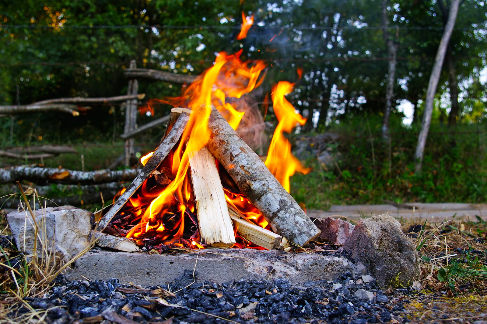 campfire set up in a pyramid formation that is burning