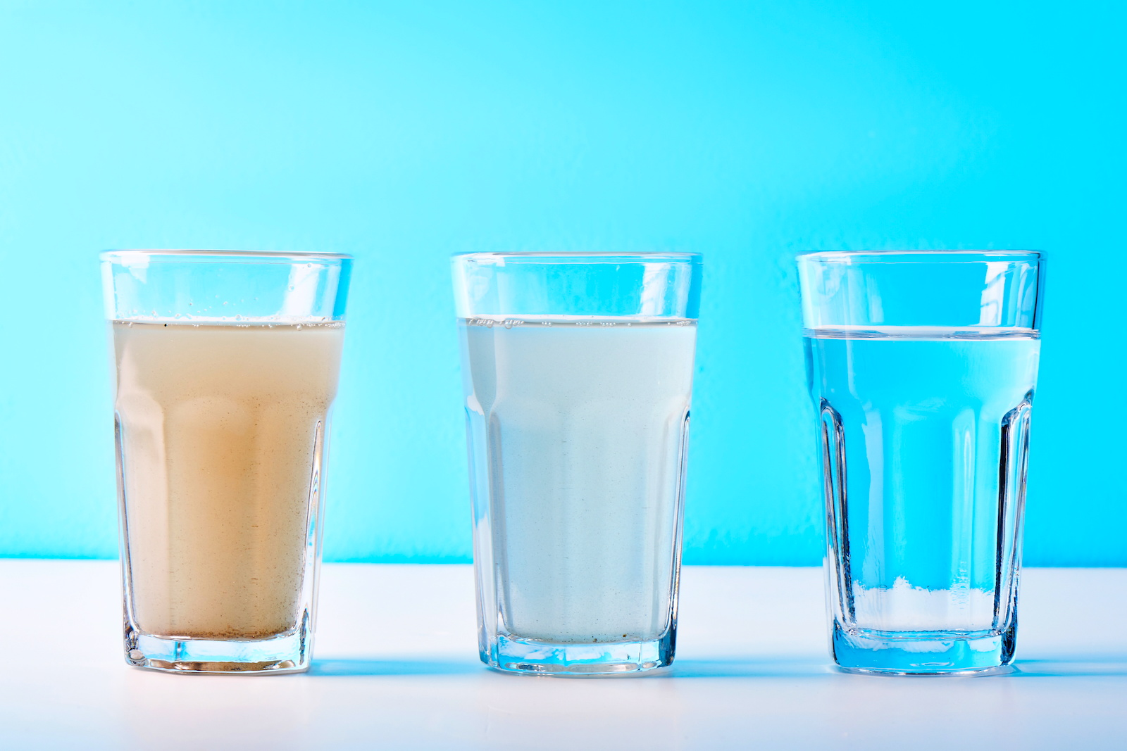 Three glasses of water starting out dirty on the left side and progressively getting cleaner in water quality