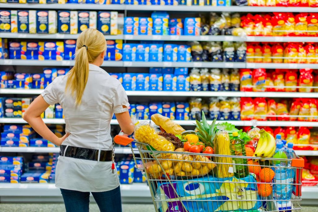 Woman next to a full shopping cart looking at grocery store shelves
