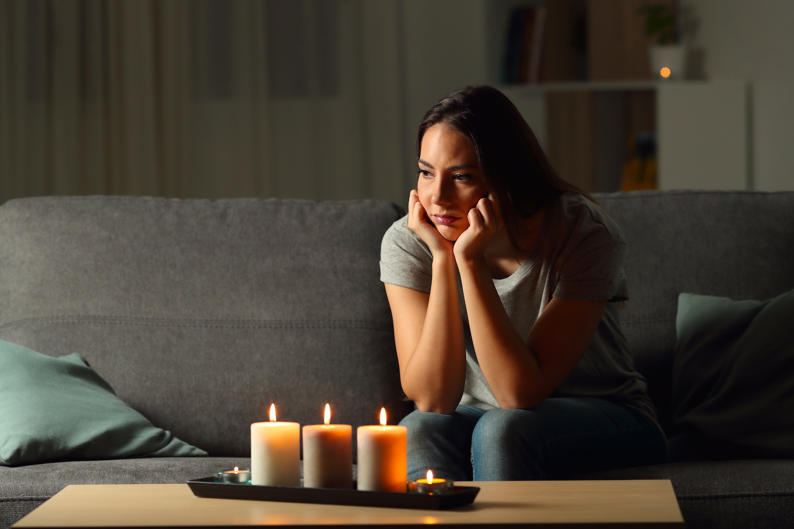 Young woman sitting next to candle light in a house without electricity