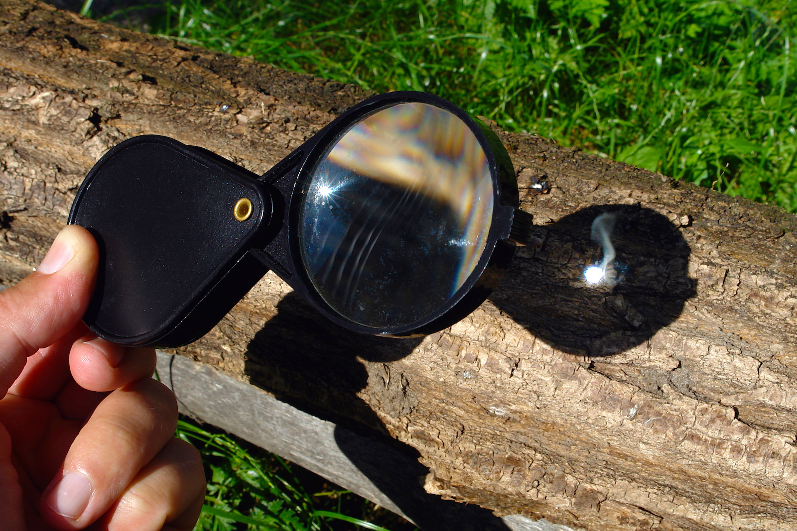 Magnifying glass reflecting the sun to start a fire on a log