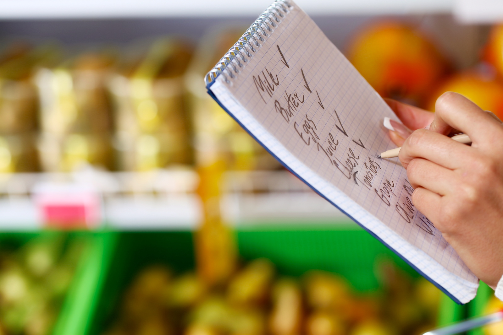 Shopping list with groceries on it while rows of food are in the background
