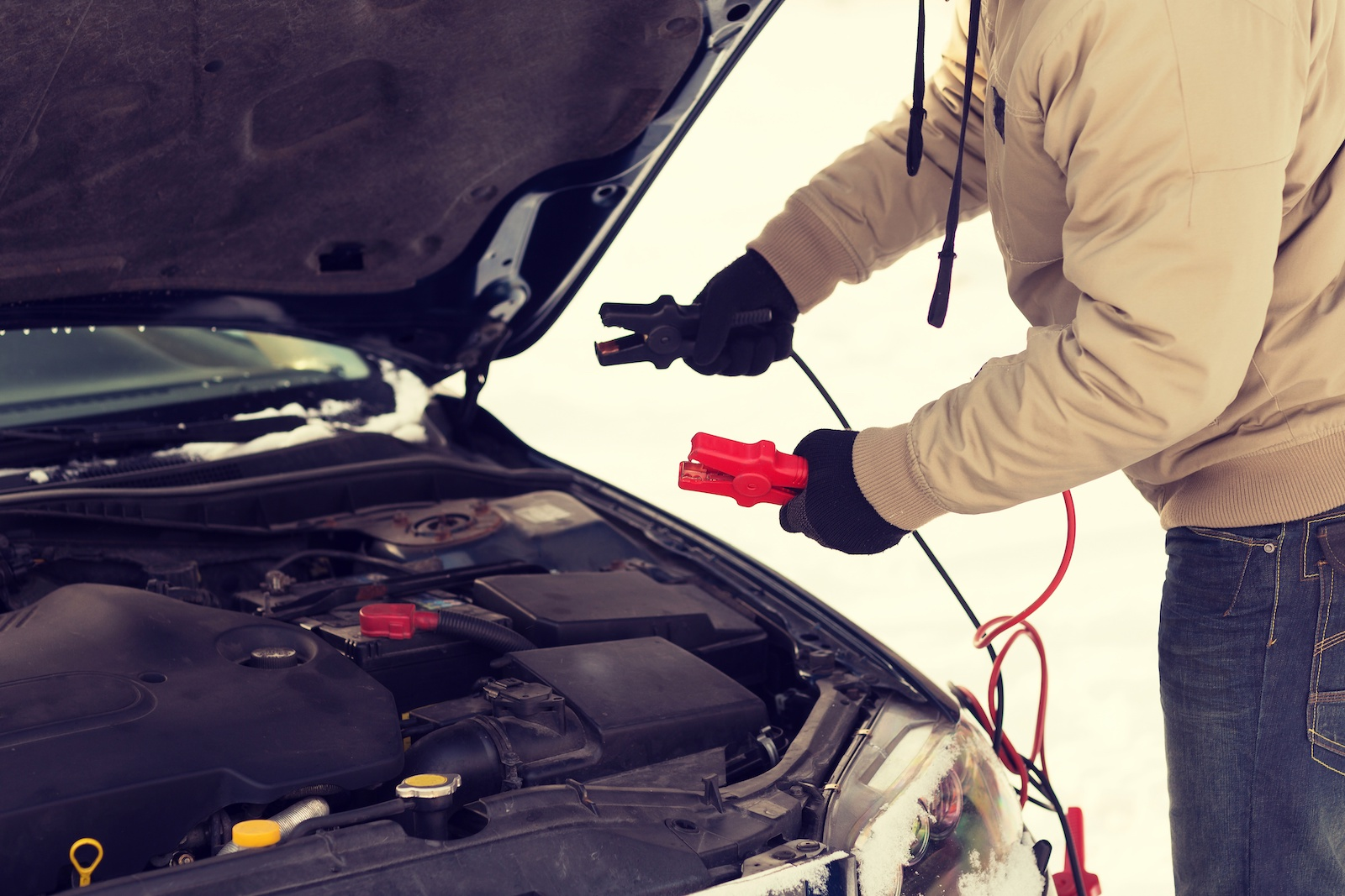 power portable jump starter being used to jumpstart a car